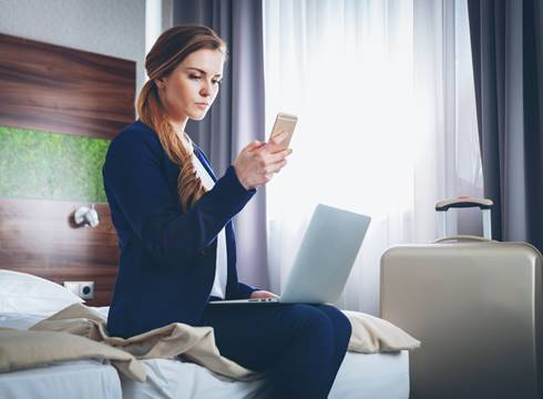 Woman in hotel room looking at hotel app